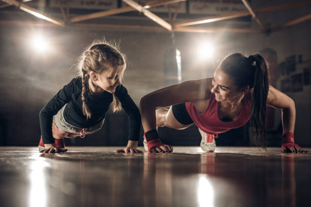 Happy female coach and little girl doing push-ups in a health club. stock photo