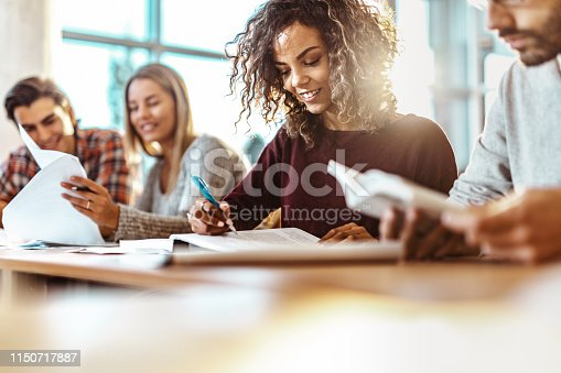 Happy African American female student reading a lecture from a book on a class in the classroom. Copy space.
