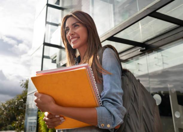 glücklich weibliche college-student lächelnd - öffentliches gebäude stock-fotos und bilder