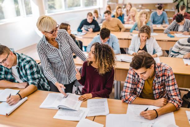 happy female college student talking to senior professor on a class in the classroom. - professore foto e immagini stock
