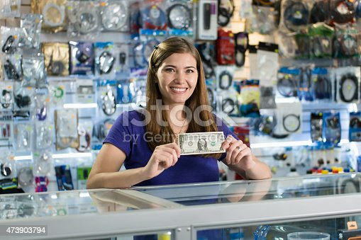 Young white woman working as shop owner in computer store, showing her first dollar to the camera and smiling. Rack focus from woman's face to banknote