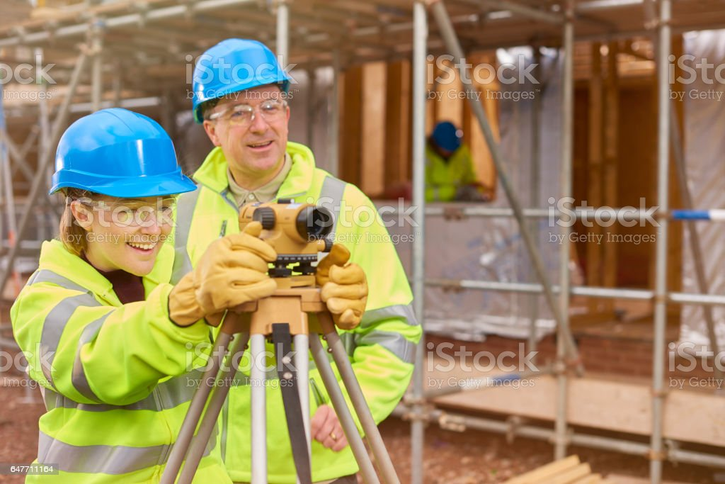 happy female construction trainee with tutor stock photo