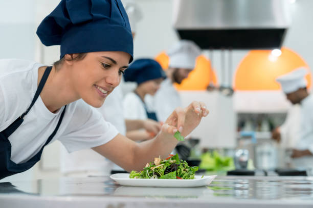 glückliche köchin hinzufügen von details zu einem salat vorbereitet sie nur lächelnd - erdnusssalatdressings stock-fotos und bilder