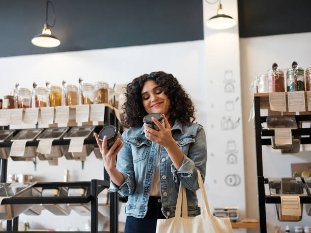 Happy female costumer holding jars in eco-friendly store stock photo