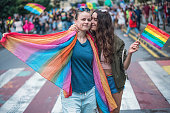 Beautiful young females marching at the gay pride, looking at camera and hugging