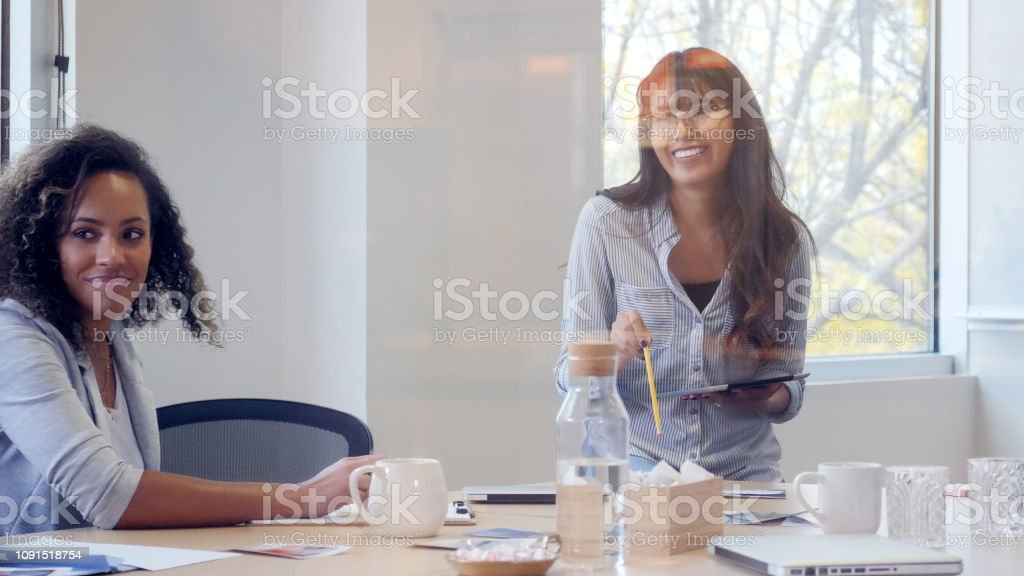 Young female creative professional gestures while giving a...