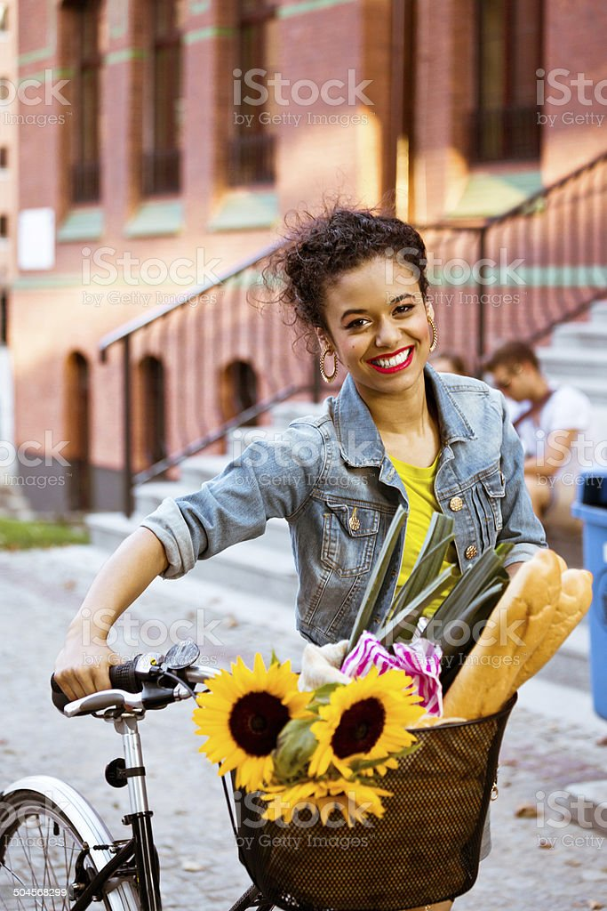 Happy female cyclist Young woman standing with bicycle with groceries in basket and smiling at camera. 20-24 Years Stock Photo