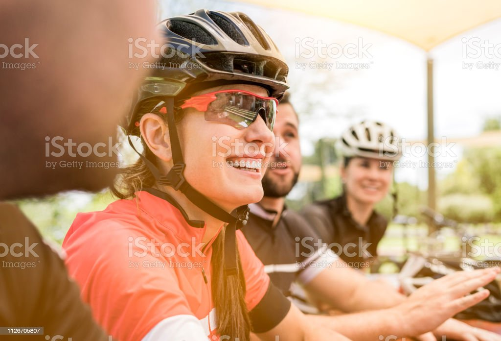 Glückliche Radfahrerin sitzt mit Freunden am Tisch – Foto