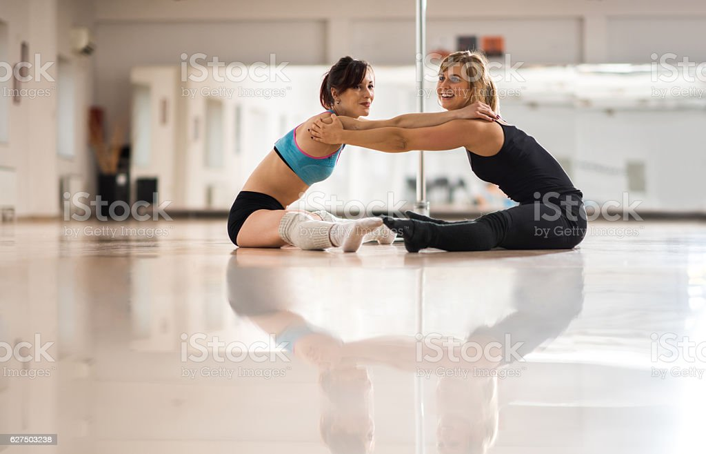 Happy female dancers stretching together in a dance studio. stock photo