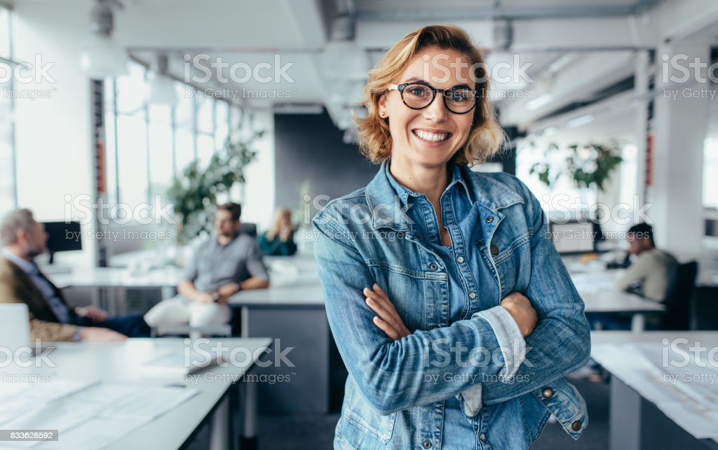 Happy female designer standing in office stock photo