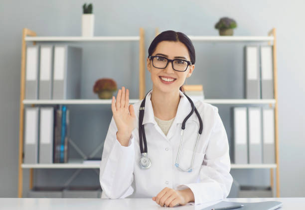 Happy female doctor on video call with client. Therapist communicating with patient online from medical office stock photo