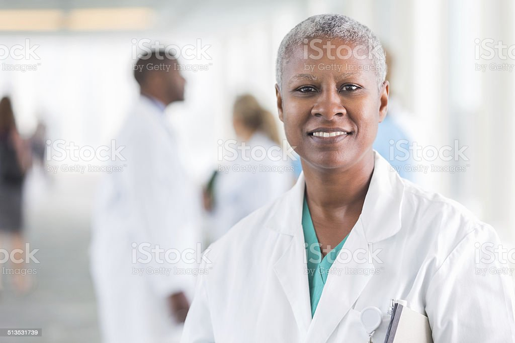 Happy female doctor smiling while walking in hospital hallway stock photo