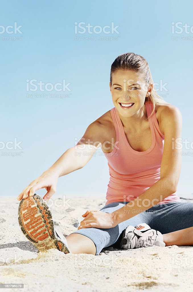 Happy female doing warmup exercise on beach royalty-free stock photo
