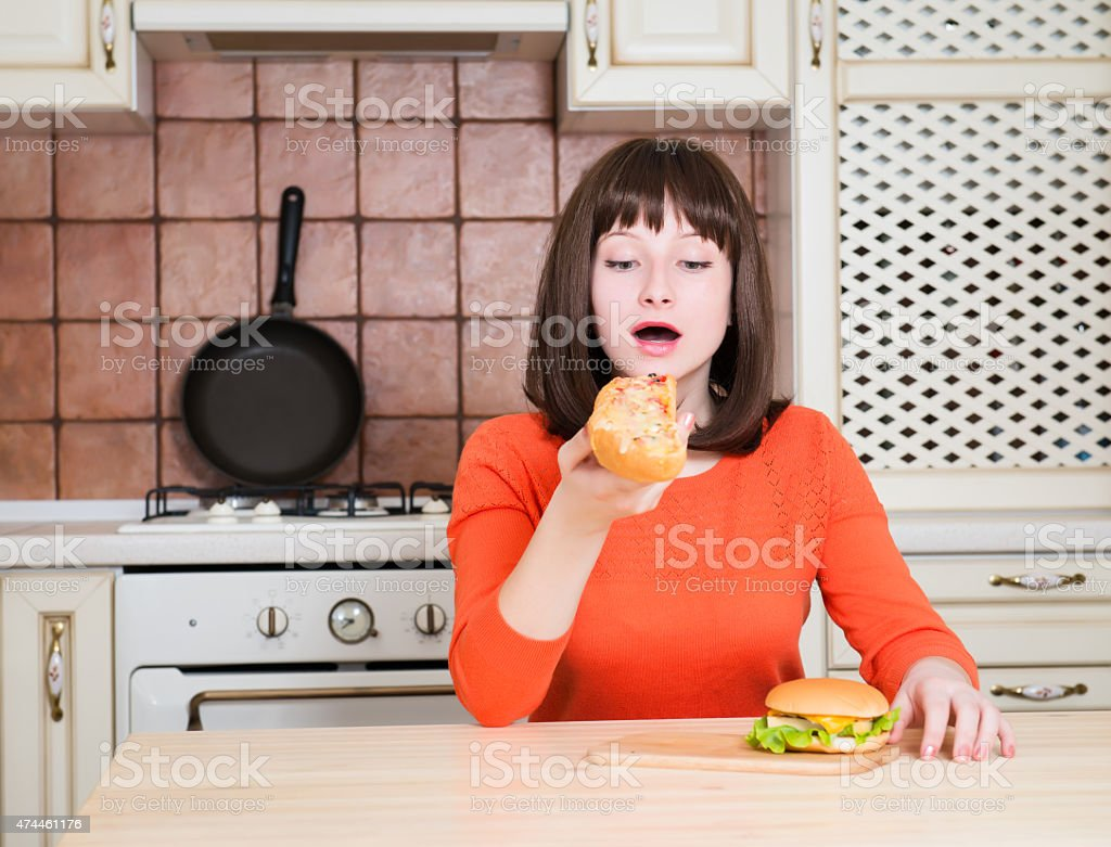 Happy female eating fast food. Woman eating french bread pizza stock photo