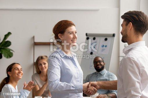 924520168 istock photo Happy female employee intern handshake helpful boss get rewarded promoted 1150384638