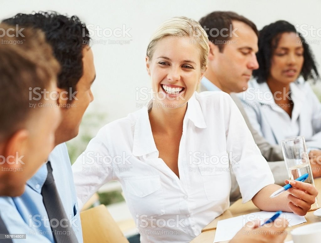 Happy female executive in discussion with colleagues royalty-free stock photo