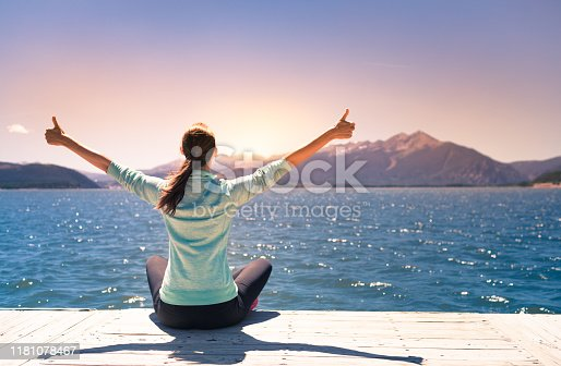 952953174 istock photo Happy female feeling free in nature next to a beautiful mountain lake. 1181078467