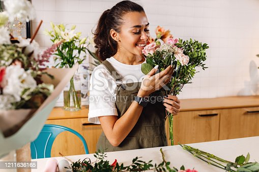 Happy female florist with a bouquet in hand. Woman with closed eyes smelling flowers.
