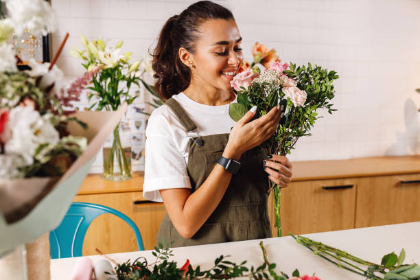 Happy female florist with a bouquet in hand. Woman with closed eyes smelling flowers. stock photo