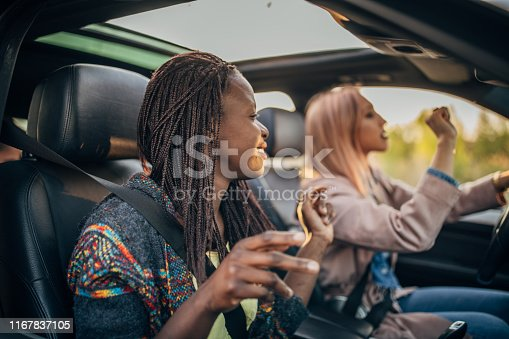 812419994 istock photo Happy female friends driving in a car 1167837105