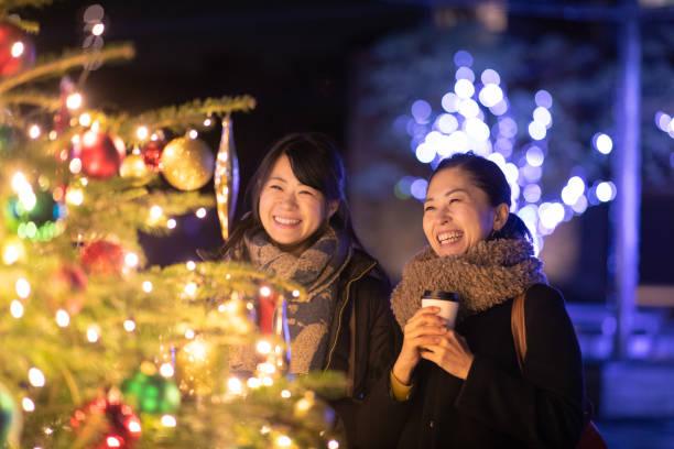 glücklich freundinnen genießen weihnachtsbeleuchtung - weihnachten japan stock-fotos und bilder