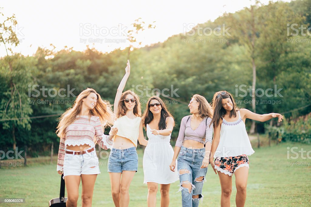 Happy female friends having fun outside in nature stock photo
