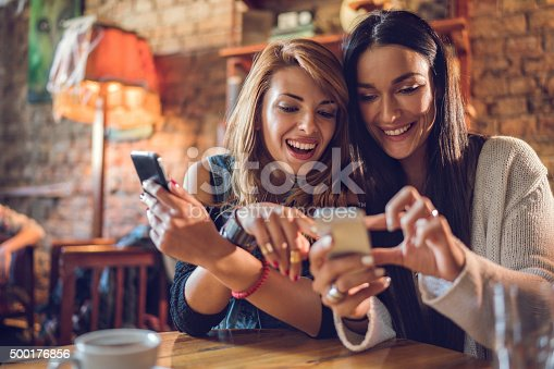 Happy women using their mobile phones while relaxing in a cafe.