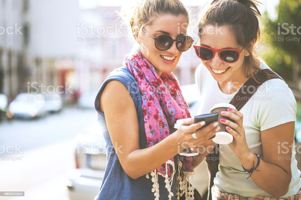 Happy female friends reading a text message outdoors - Foto stock royalty-free di Abbigliamento casual