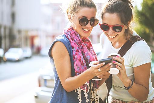 Happy Female Friends Reading A Text Message Outdoors - Fotografie stock e altre immagini di Abbigliamento casual