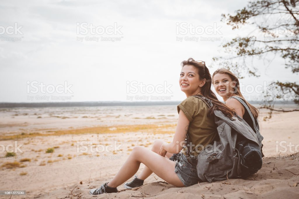 Happy female friends sitting on the desert Outdoor shot of two happy young women sitting on the dune, smiling at camera. Adolescence Stock Photo