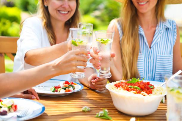 glücklich freundinnen mit gläsern limonade am esstisch in rasen - griechische partyspeisen stock-fotos und bilder
