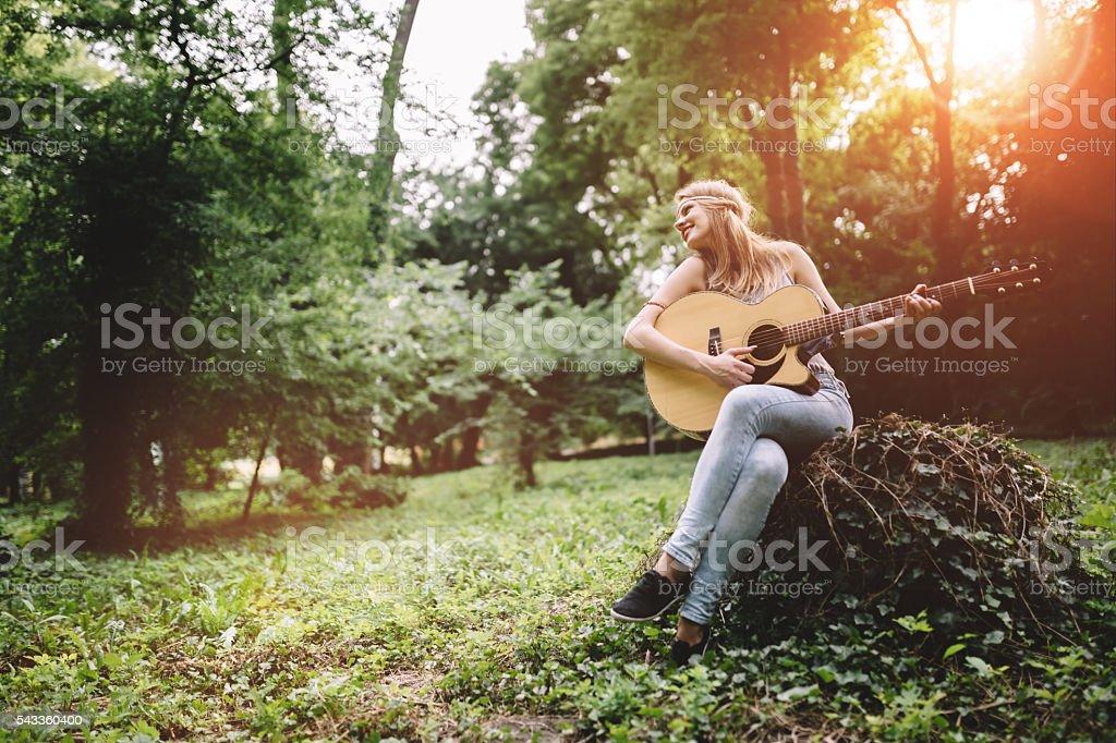 Happy female guitar player stock photo