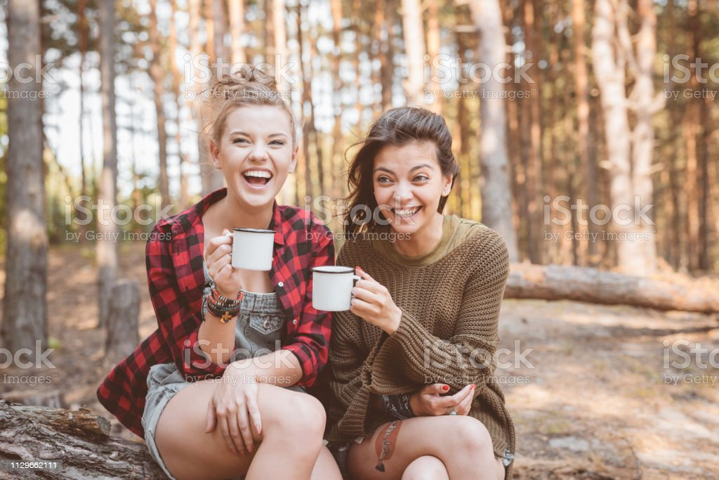 Happy female hikers are sitting with cups Beautiful young women laughing in forest. Female hikers are sitting with cups. They are enjoying summer vacation. 20-24 Years Stock Photo