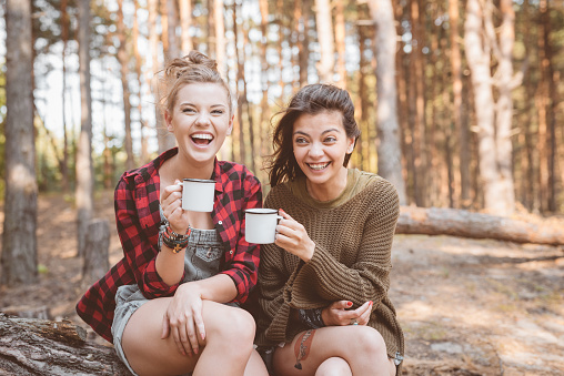 Happy Female Hikers Are Sitting With Cups Stock Photo - Download Image Now