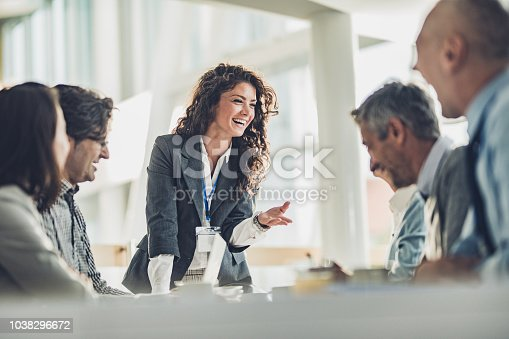 Young happy CEO communicating with her colleagues on a meeting in the office.