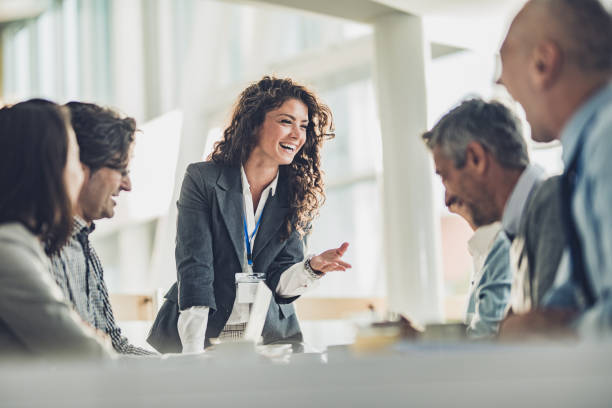 Happy female leader talking to her colleagues on a business meeting picture id1038296672?b=1&k=6&m=1038296672&s=612x612&w=0&h=09skf3bonb81q4vr3ss1 tebsv5pc4re h z6sjx0i4=