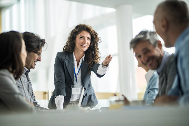 Happy female leader talking to her colleagues on a business meeting in the office. stock photo