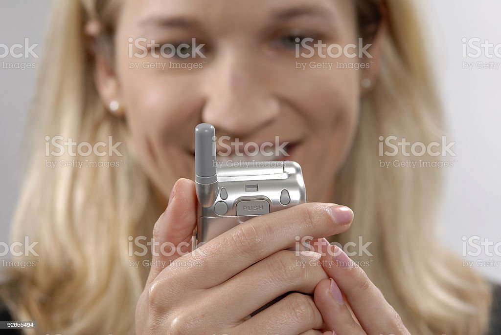 Happy female looking at cell phone stock photo