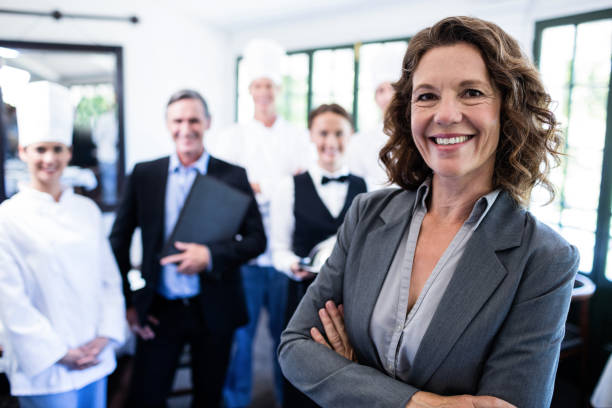 happy female manager standing with arms crossed - 40 49 years stock pictures, royalty-free photos & images