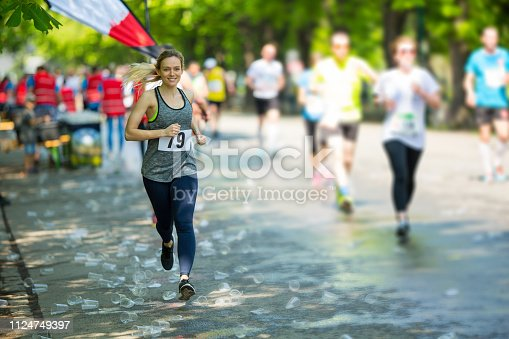 smiling young woman with start number running marathon race on sunny day shortly after refreshment stop with many empty plastic cups laying on street other participants blurred