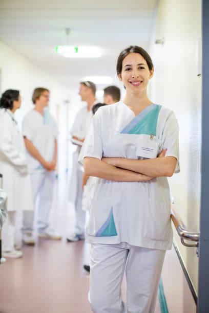 happy female nurse standing in hospital corridor - female nurse stock photos and pictures