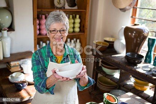 istock Happy female potter holding bowl 652242168