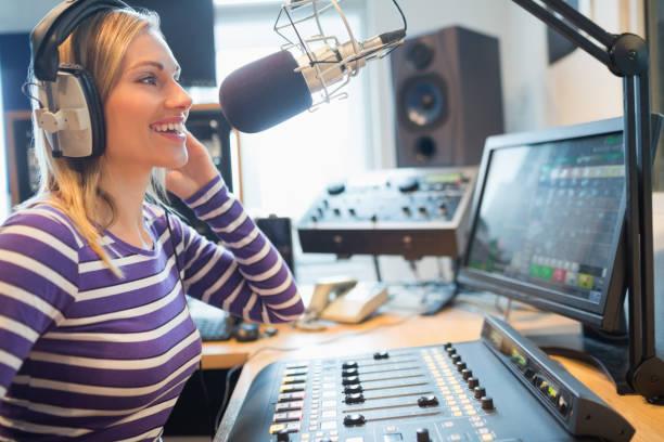 happy female radio host broadcasting in studio - talk in a radio foto e immagini stock