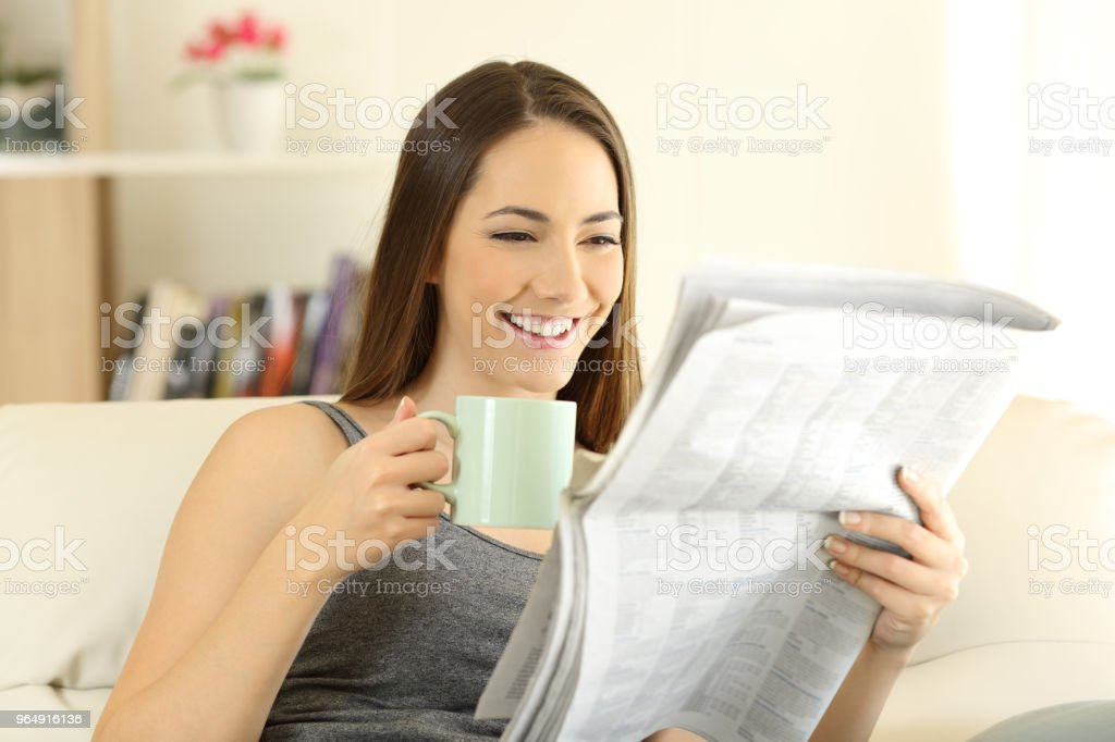 Happy female reading a newspaper on a couch royalty-free stock photo