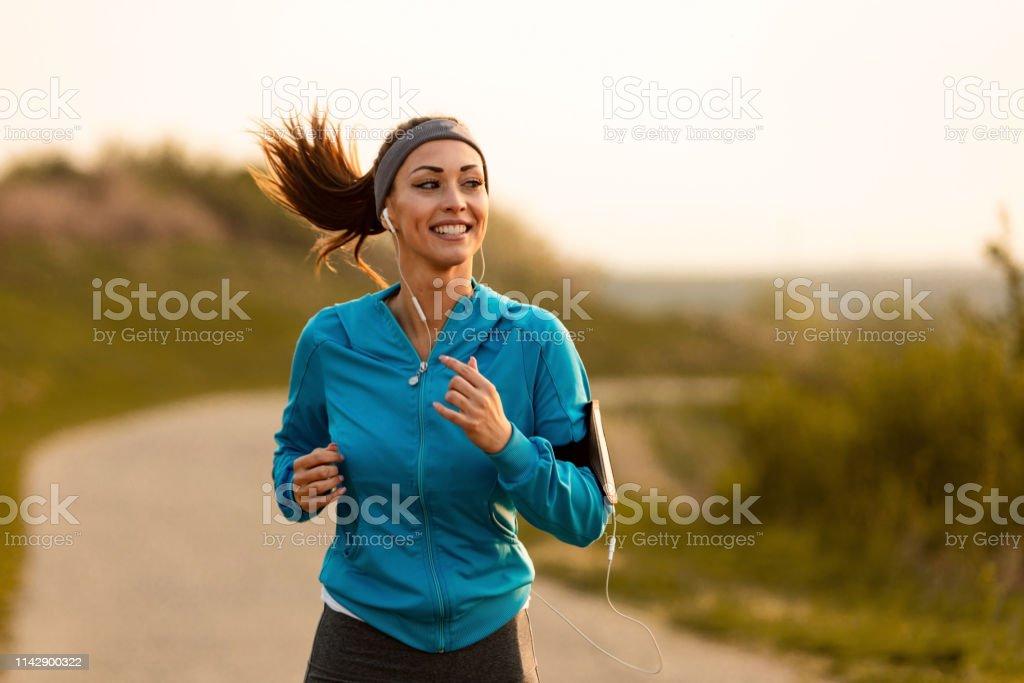 Happy female runner jogging in the morning in nature. - Foto stock royalty-free di Abbigliamento sportivo