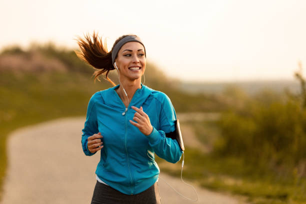 Happy female runner jogging in the morning in nature. Dedicated athletic woman running in nature and dawn. leisure equipment stock pictures, royalty-free photos & images