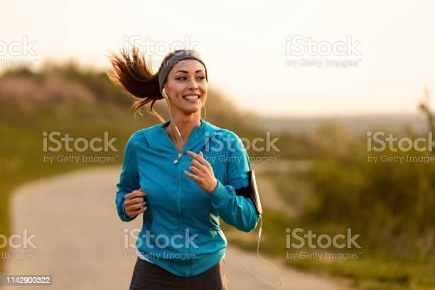 Photo libre de droit de Coureur Féminin Heureux De Jogging Le Matin Dans La Nature banque d'images et plus d'images libres de droit de Activité