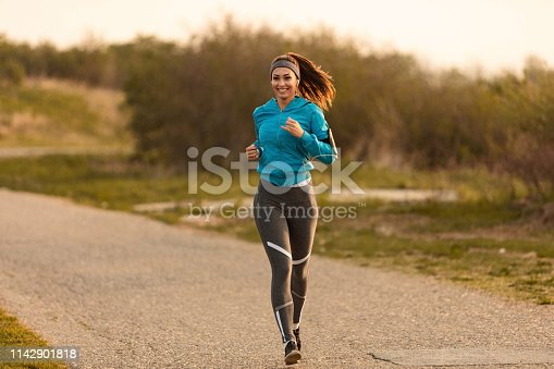 1142900322 istock photo Happy female runner jogging on the road. 1142901818