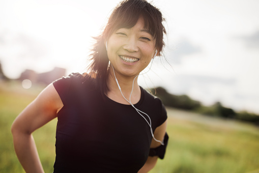 istock Happy female running standing outdoors and smiling 601912026