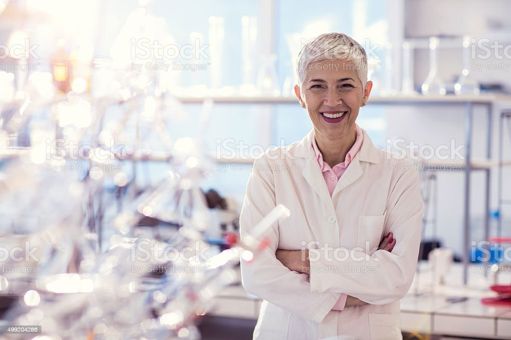 Happy female scientist with crossed arms in the laboratory. stock photo